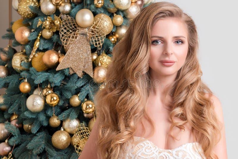 Lycklig kvinna på dekorerad guld- julgranbakgrund Lyxig blond flicka Beröm för glad jul och för lyckligt nytt år dem royaltyfri foto
