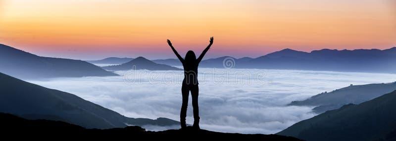 Lycklig kvinna på en bergstopp ovanför dimman royaltyfri foto
