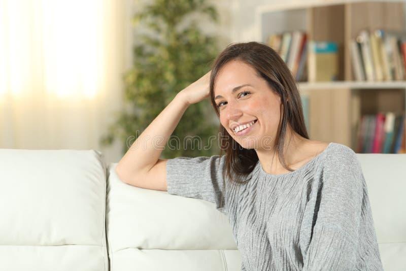 Lycklig kvinna på en soffa hemma som ser kameran royaltyfri foto