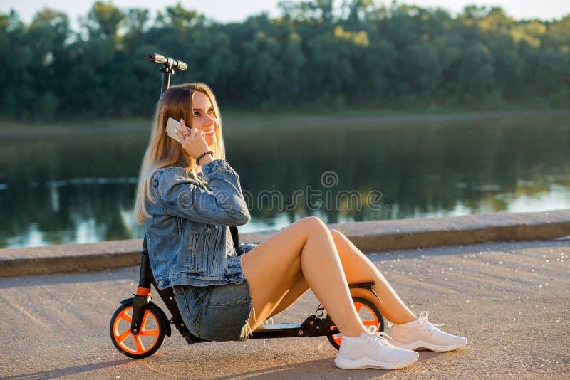 Lycklig kvinna på en sparkcykel som talar på telefonen och skrattar i natur royaltyfri bild