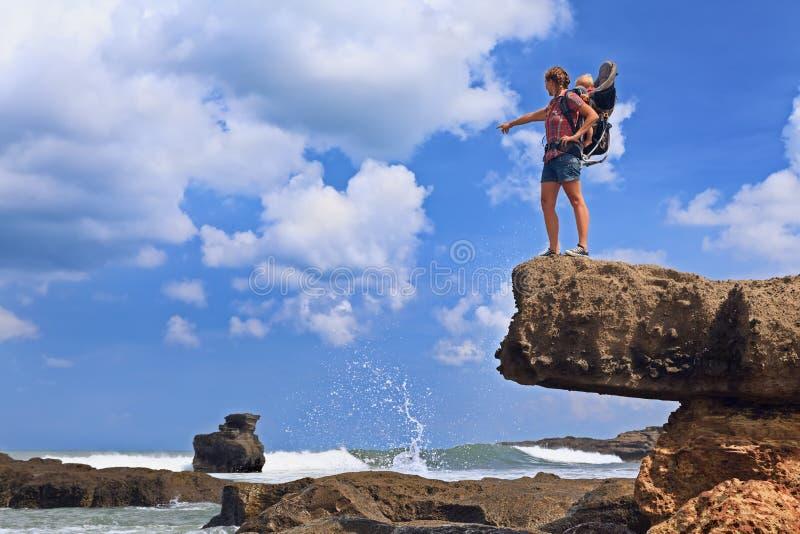 Lycklig kvinna på havsklippan med barnet i ryggsäckbärare royaltyfri bild