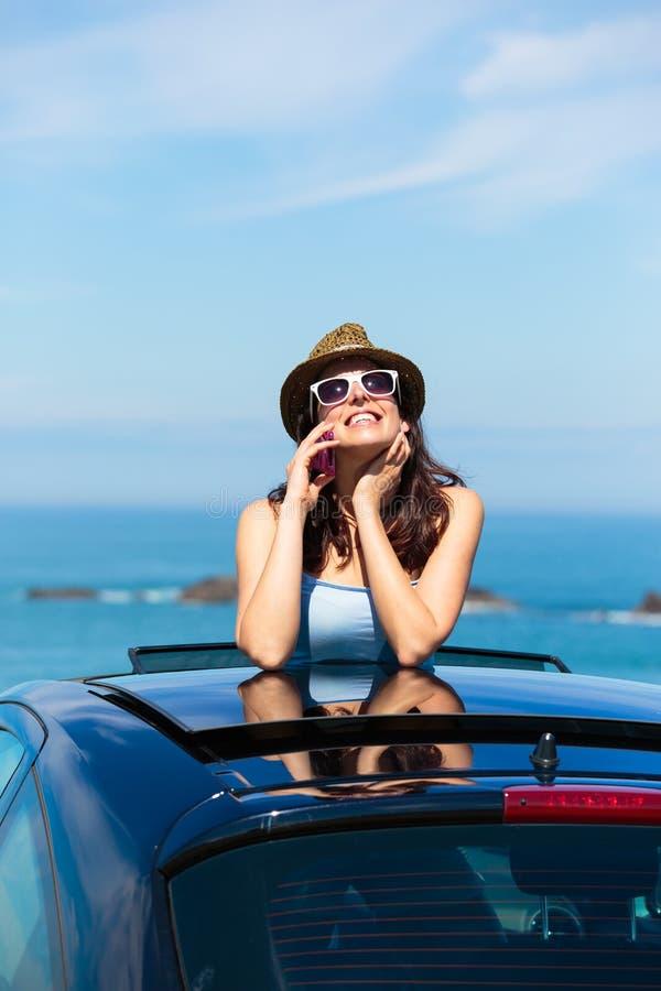 Lycklig kvinna på lopp för sommarbilsemester som talar på mobiltelefonen royaltyfri foto