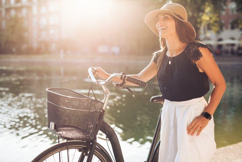 Lycklig kvinna på parkera med en cykel royaltyfri foto