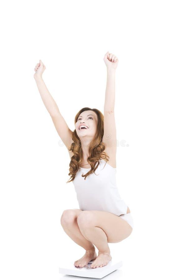 Lycklig kvinna på skala royaltyfria foton