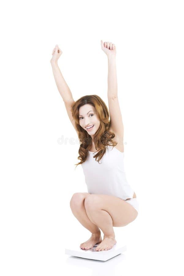 Lycklig kvinna på skala royaltyfria bilder