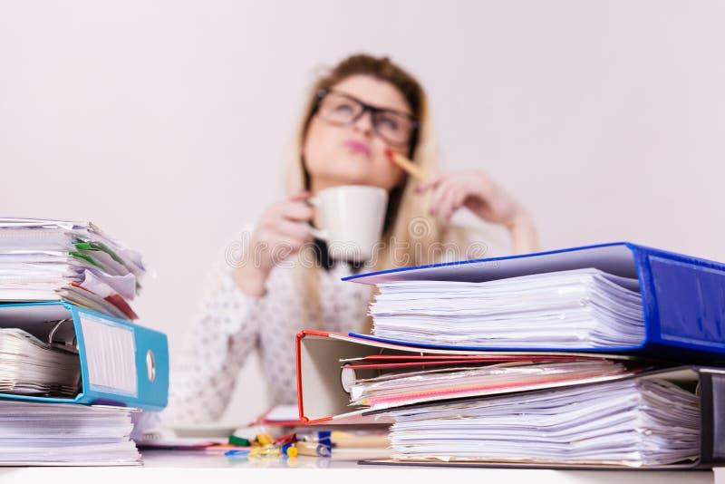 Lycklig kvinna p? kontoret som dricker varmt kaffe arkivfoton