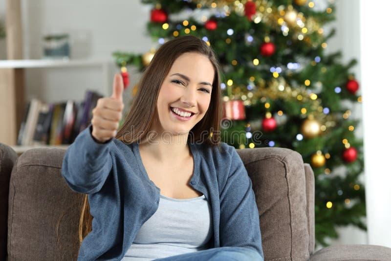 Lycklig kvinna som är hemmastadd i jul med tummar upp arkivfoton