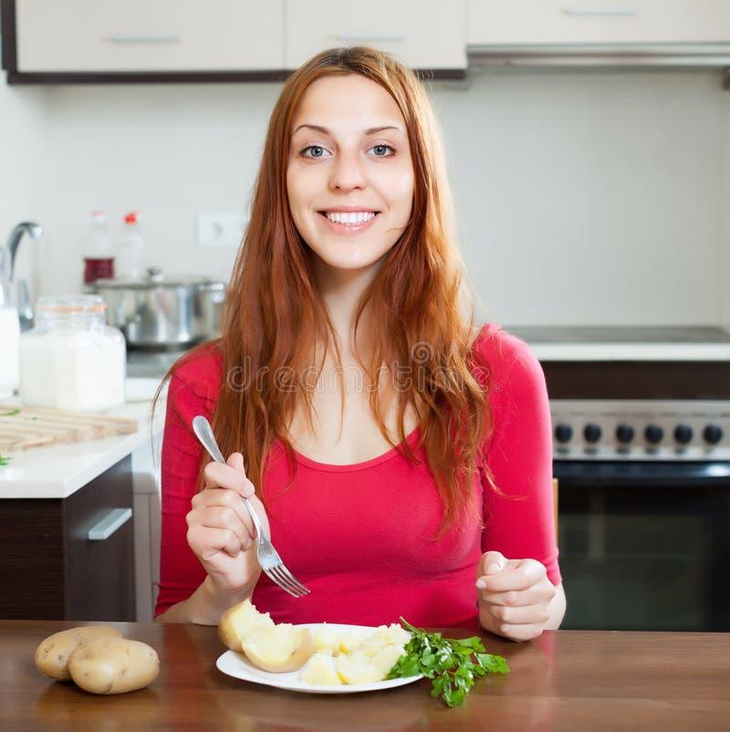 Lycklig kvinna som äter omslagspotatisar royaltyfri foto