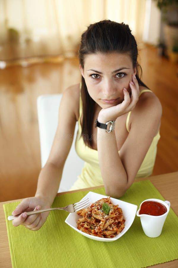 Lycklig kvinna som äter pasta arkivbilder