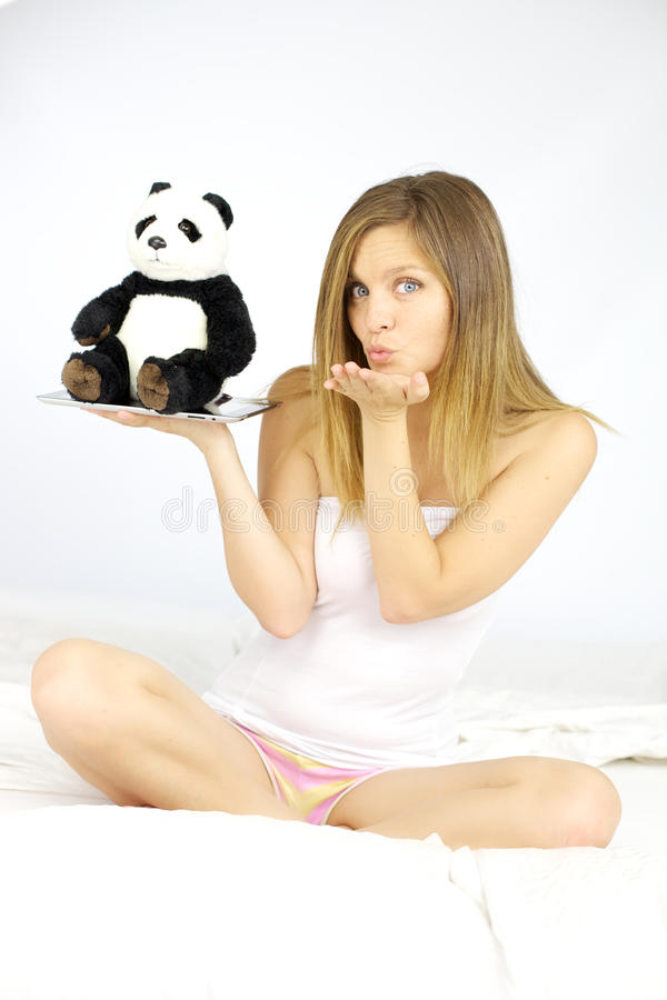 Lycklig kvinna som överför kyssen med pandan och minnestavlan i hand arkivbilder