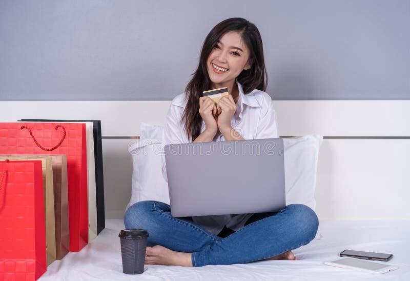 Lycklig kvinna som använder bärbar datordatoren för online-shopping med credi arkivfoto