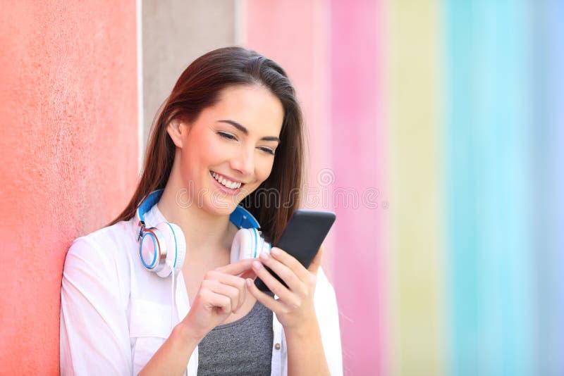 Lycklig kvinna som anv?nder den smarta telefonen som lutar i en v?gg royaltyfri foto