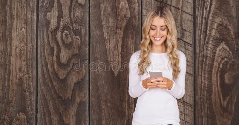 Lycklig kvinna som använder den smarta telefonen mot träväggen stock illustrationer
