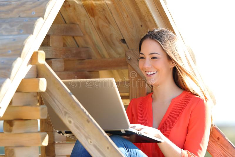Lycklig kvinna som använder en bärbar dator i ett trähus arkivfoton