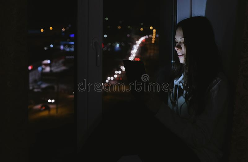 Lycklig kvinna som använder minnestavlan för videopn prata Sitta på fönsterbrädan i mörkret på natten arkivfoton