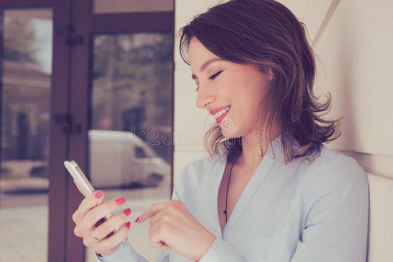 Lycklig kvinna som använder mobiltelefonanseende utanför lägenhetskomplexet arkivbilder
