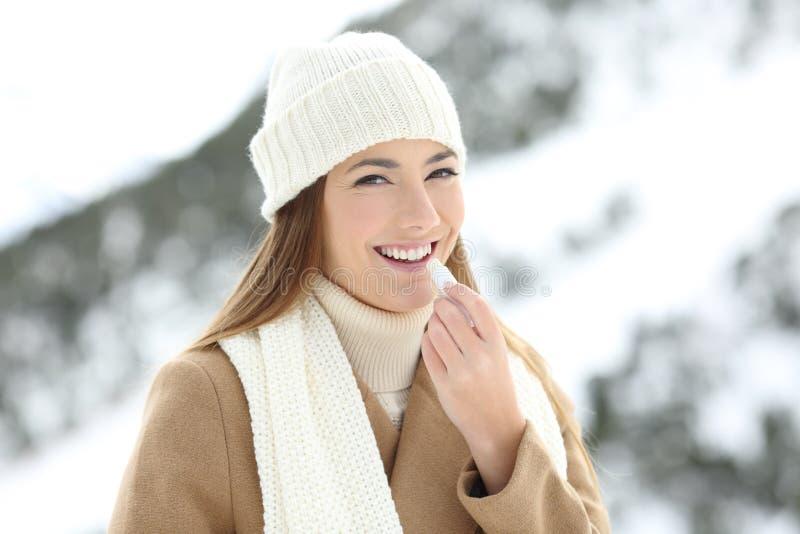 Lycklig kvinna som applicerar kantbalsam i vinterferie royaltyfri fotografi