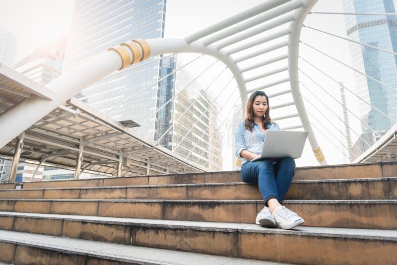 Lycklig kvinna som arbetar med b?rbara datorn Lyckad och lyckabegrepp Teknologi- och livsstilbegreppsstad och stads- tema Lycklig fotografering för bildbyråer