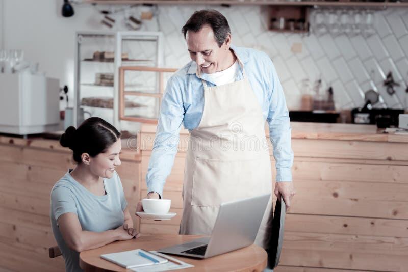 Lycklig kvinna som arbetar på en bärbar dator och en uppassare som kommer med henne kaffe fotografering för bildbyråer