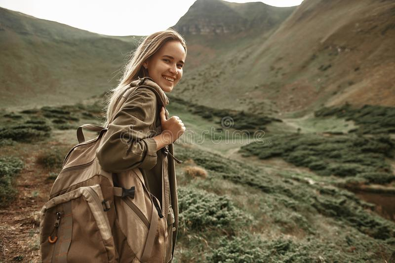 Lycklig kvinna som bär den stora ryggsäcken och att le royaltyfria bilder