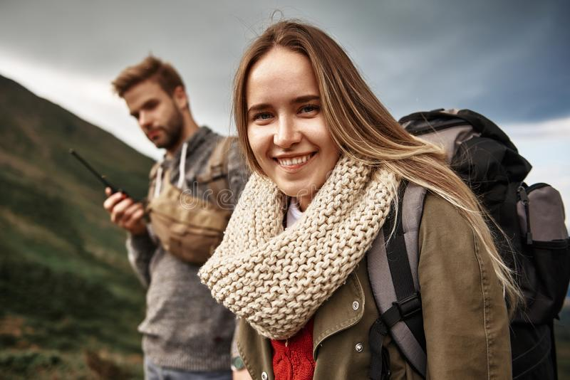Lycklig kvinna som bär varm kläder och ler, medan resa arkivfoto