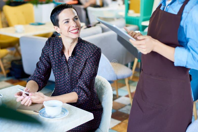 Lycklig kvinna som beställer i kafé fotografering för bildbyråer