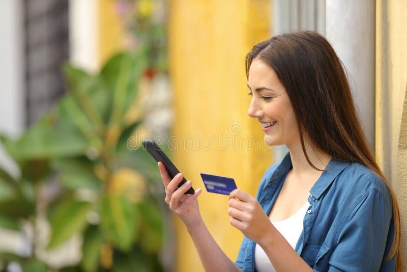Lycklig kvinna som betalar direktanslutet genom att använda kreditkorten royaltyfri bild