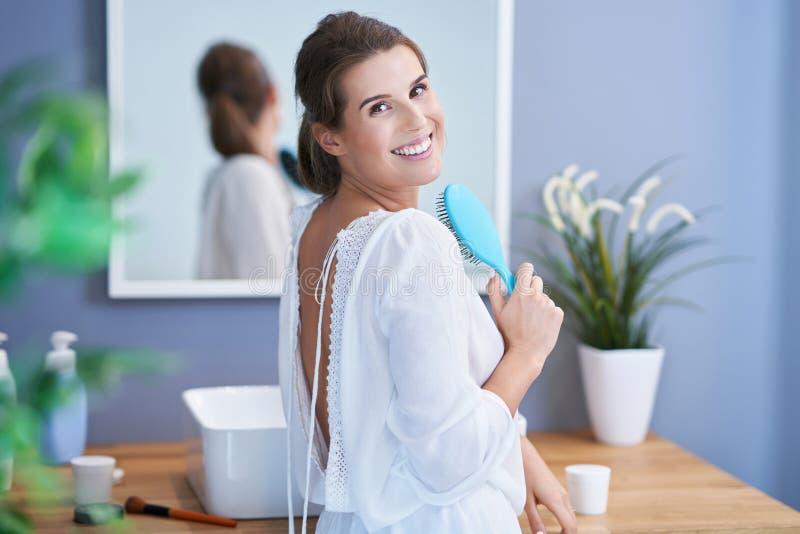 Lycklig kvinna som borstar hår i badrum royaltyfri bild