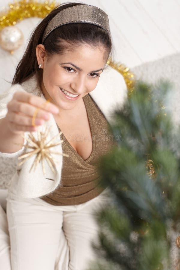 Lycklig kvinna som dekorerar julträdet royaltyfri foto