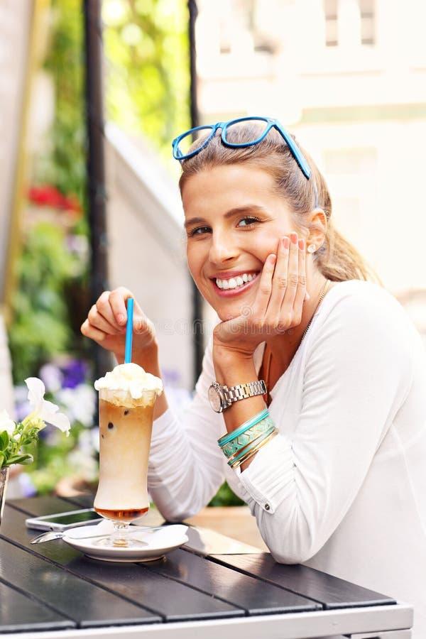 Lycklig kvinna som dricker frappe i kafé royaltyfria foton
