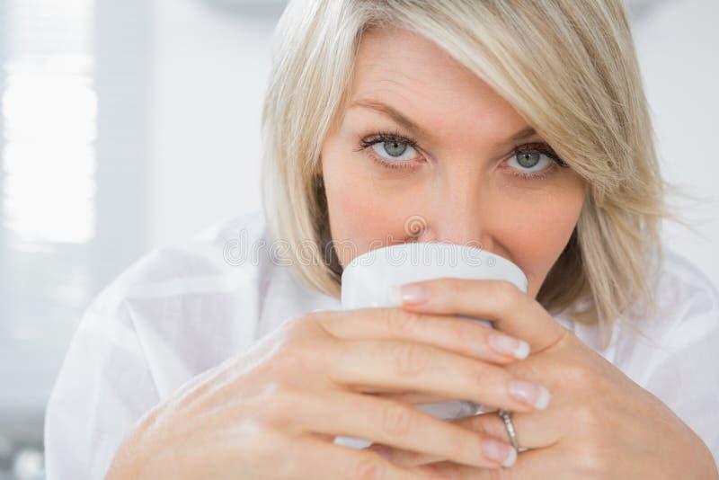 Lycklig kvinna som dricker kaffe i morgonen royaltyfria bilder