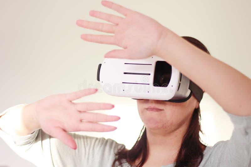 Lycklig kvinna som får erfarenhet genom att använda VR-hörlurar med mikrofonexponeringsglas av den faktiska verklighetbilden royaltyfri fotografi