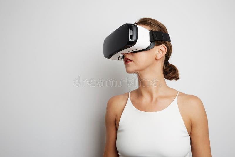 Lycklig kvinna som får erfarenhet genom att använda VR-hörlurar med mikrofonexponeringsglas av gestikulera händer för virtuell ve fotografering för bildbyråer