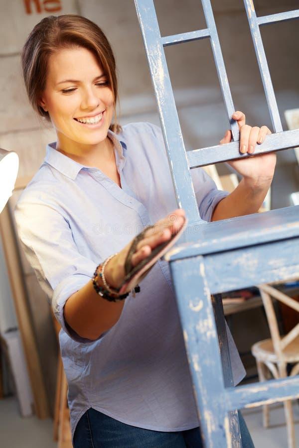 Lycklig kvinna som förnyar stol arkivbild