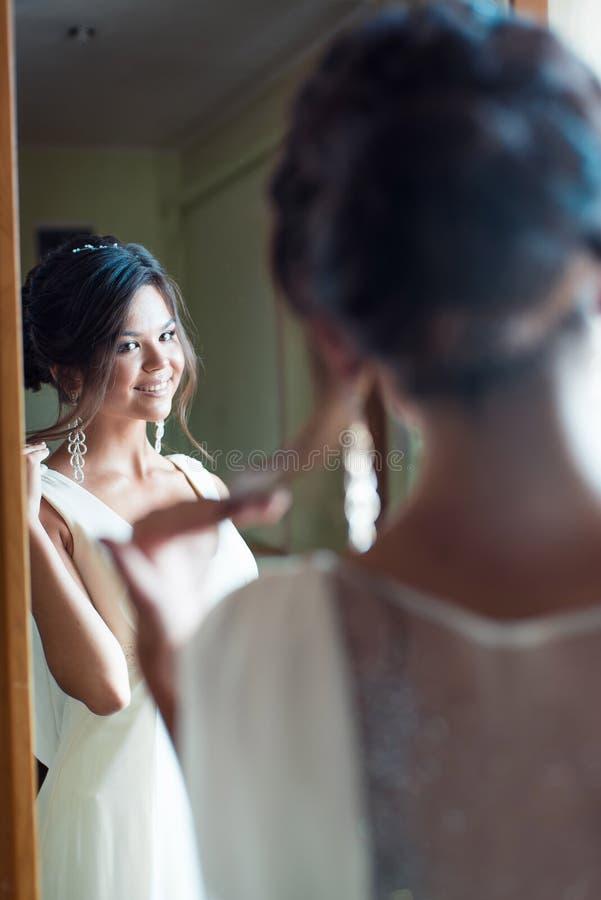 Lycklig kvinna som försöker på den nya klänningen i visningslokal Mode- och valbegrepp arkivbilder