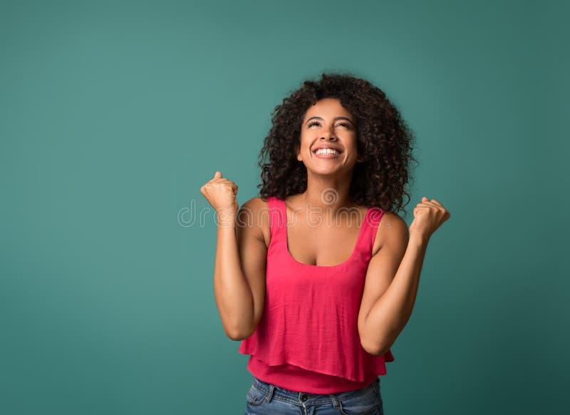 Lycklig kvinna som firar hennes framgång på blå bakgrund royaltyfri foto