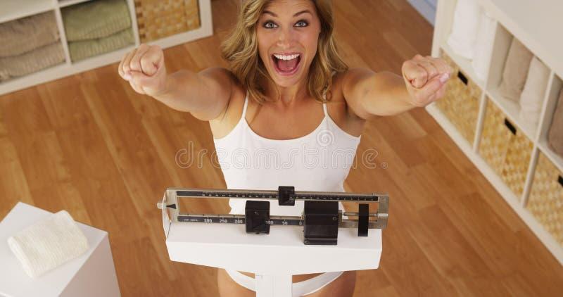 Lycklig kvinna som firar viktförlust royaltyfria bilder