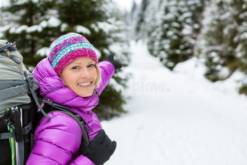 Lycklig kvinna som fotvandrar i den vita snöig vinterskogen med ryggsäcken royaltyfri foto
