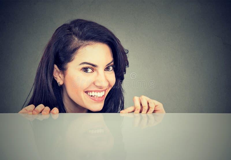 Lycklig kvinna som från under kikar tabellen royaltyfri bild