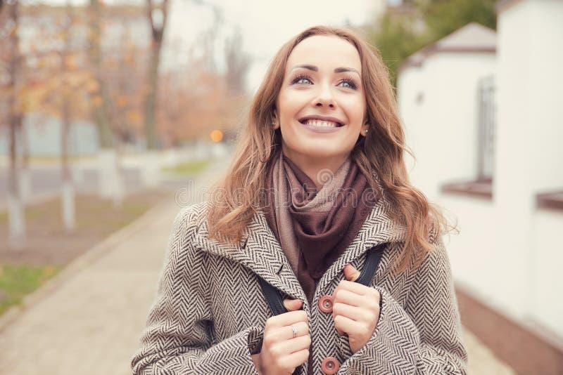 Lycklig kvinna som går på en gata i drömmar royaltyfri foto