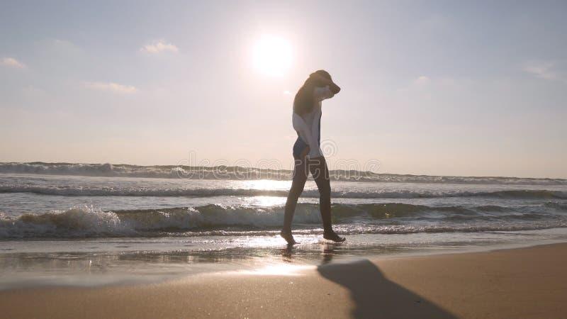 Lycklig kvinna som går på stranden av havet och besprutar vattnet med hennes fot Ung härlig flicka som tycker om liv royaltyfri fotografi