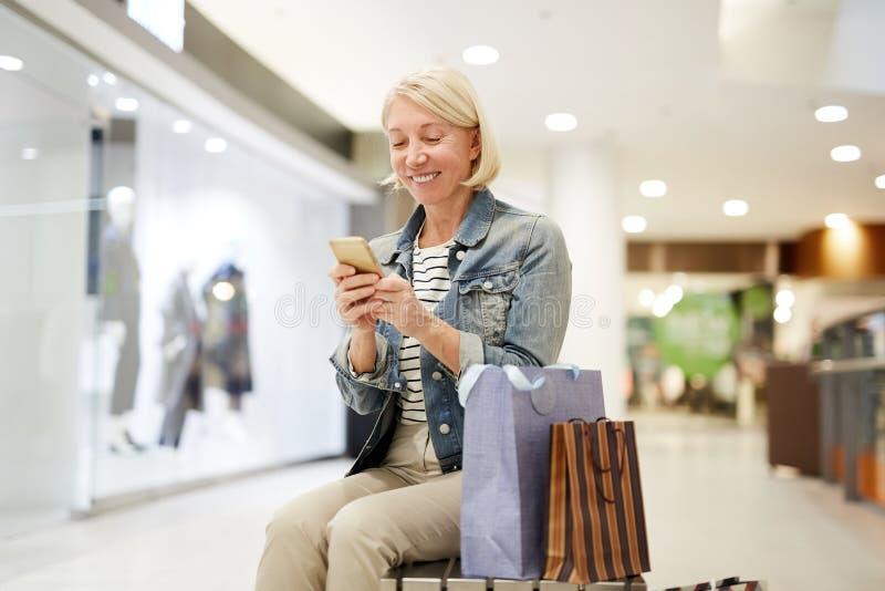 Lycklig kvinna som gör stolpen om shopping på socialt massmedia royaltyfri fotografi