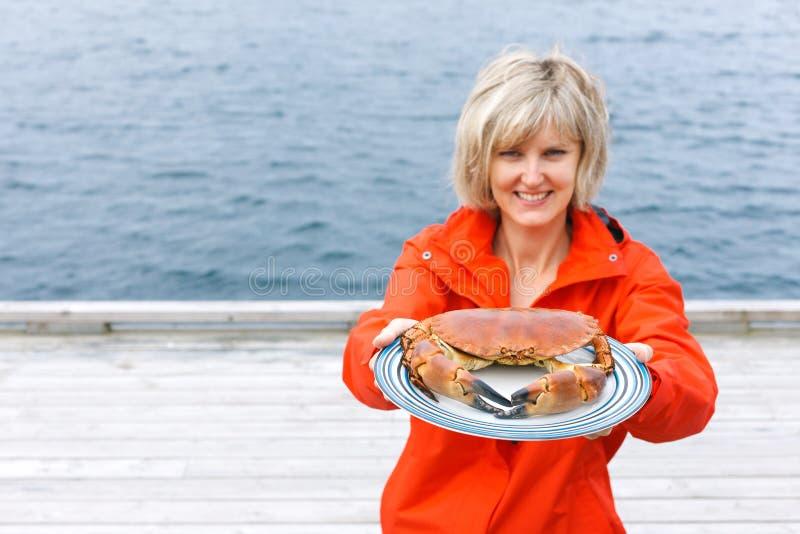 Lycklig kvinna som ger den lagade mat krabban på plattan arkivfoton