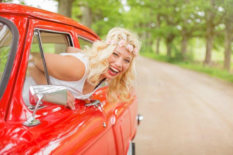 Lycklig kvinna som hänger ut ur tappningbilen arkivbilder