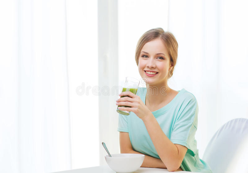 Lycklig kvinna som har frukosten hemma arkivbilder