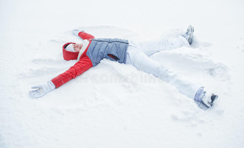 Lycklig kvinna som har gyckel på insnöad vinter royaltyfri fotografi