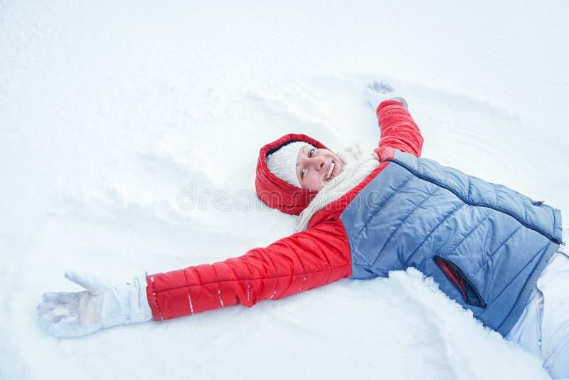 Lycklig kvinna som har gyckel på insnöad vinter arkivbild