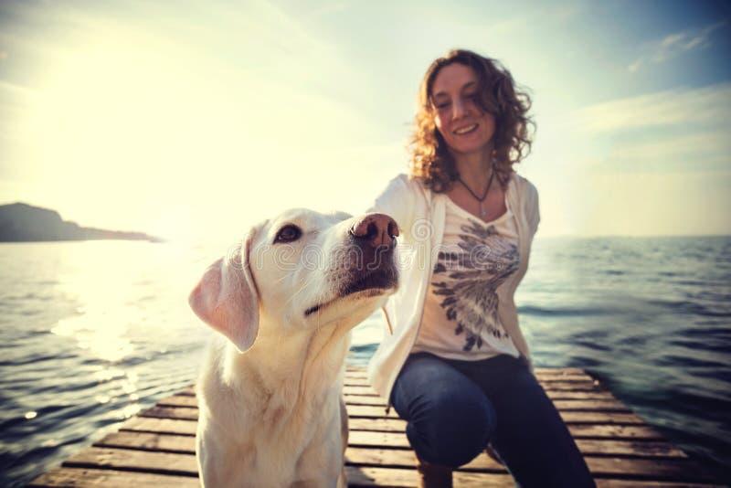 Lycklig kvinna som har gyckel samman med hennes hund royaltyfri bild
