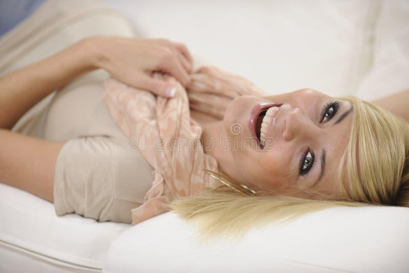 Lycklig kvinna som hemma kopplar av att skratta royaltyfri fotografi
