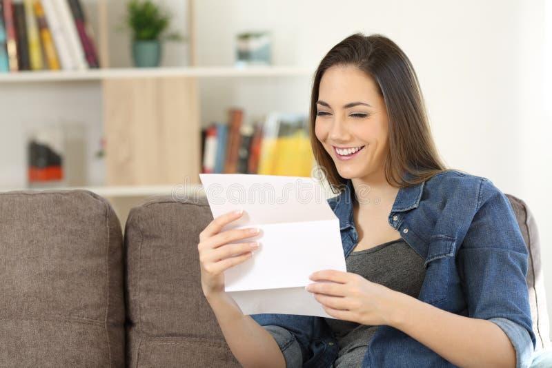 Lycklig kvinna som hemma läser ett brev på en soffa royaltyfria bilder